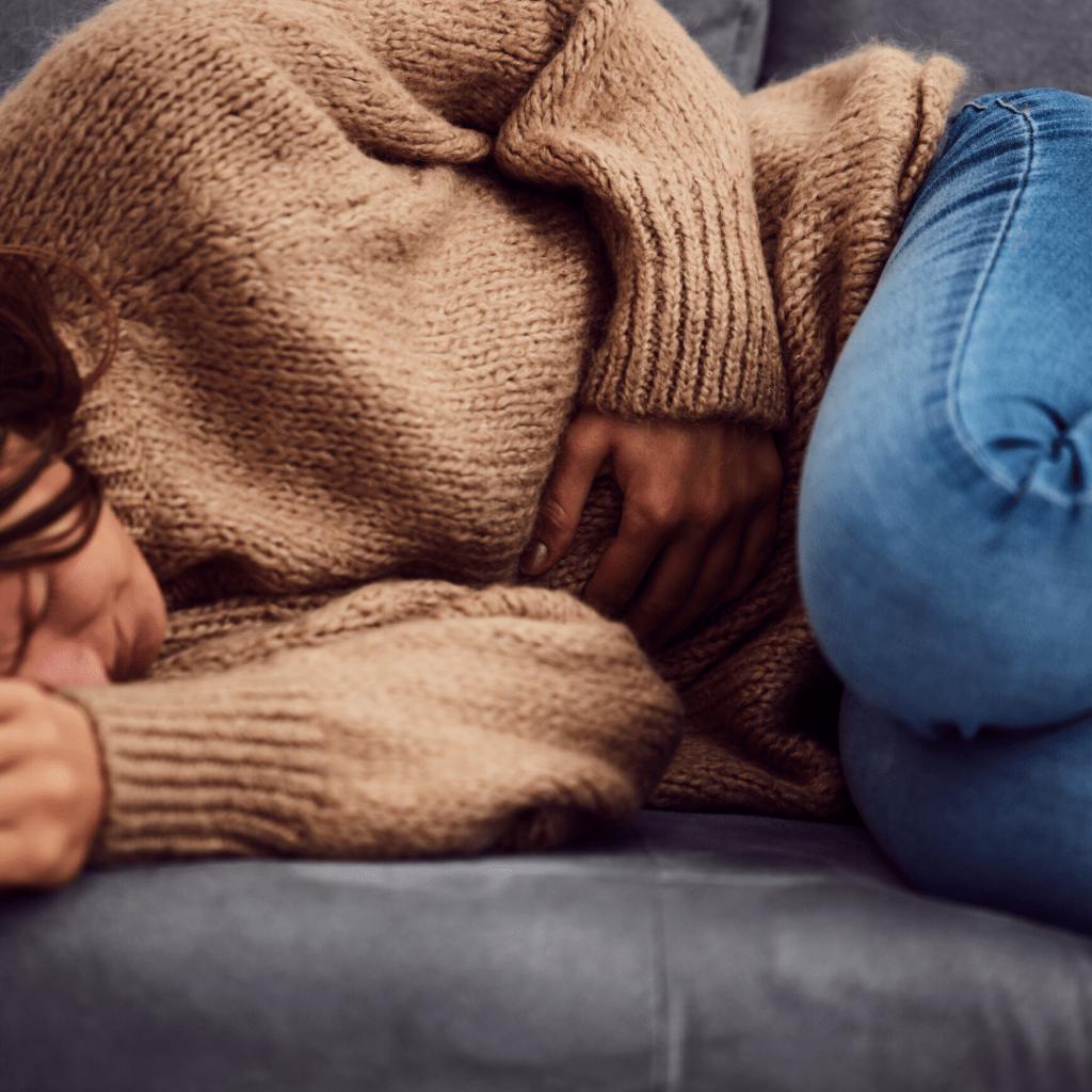 Frau liegt mit Periodenschmerzen auf dem Sofa